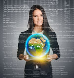 Smiling woman holding Earth globe over tablet on Royalty Free Stock Images