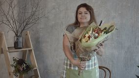 Smiling woman holding edible bouquet arrangement. Cheerful redhead woman in apron holding tasty assembled edible bouquet arrangement wrapped in kraft paper for a stock video