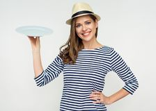 Smiling woman holding empty white plate. Isolated portrait of casual dressed woman Royalty Free Stock Images