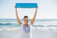 Smiling woman holding exercise mat over her head Royalty Free Stock Images