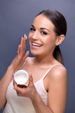 Smiling woman holding face cream Stock Photos
