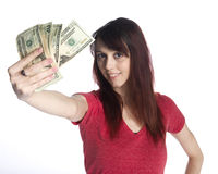 Smiling Woman Holding a Fan of 20 US Dollar Bills. Close up Smiling Young Woman in Casual Red Shirt Showing a Fan of 20 US Dollar Bills While Looking at the Royalty Free Stock Photography