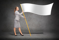 Smiling woman holding flagpole with white flag. Business and advertisement concept - smiling woman holding flagpole with white flag royalty free stock photo