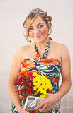 Smiling woman holding flowers. Attractive young woman in tiara and  colorful dress holding bunch of flowers and silver evening bag Royalty Free Stock Images