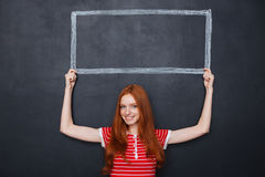 Smiling woman holding frame drawn on blackboard above her head Royalty Free Stock Image