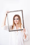 Smiling woman holding a frame in hands Royalty Free Stock Images