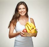 Smiling woman holding fruit set in straw basket. Portrait of girl with banana, apples and citrus Stock Image