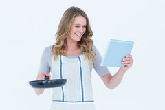 Smiling woman holding frying pan and tablet pc Royalty Free Stock Photo