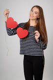 Smiling woman holding garland of two red paper hearts Stock Images