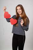 Smiling woman holding garland of two red paper hearts Royalty Free Stock Photography