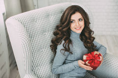 Smiling woman holding a gift box heart. Valentine's Day. Royalty Free Stock Photography