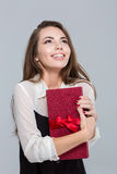 Smiling woman holding gift box and looking up Royalty Free Stock Images