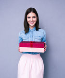 Smiling woman holding gift and looking at camera Stock Image
