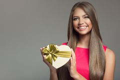 Young smiling woman holding gift. Valentine day. Stock Image