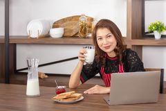 Smiling woman and holding a glass of milk stock image