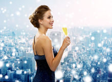 Smiling woman holding glass of sparkling wine. Drinks, christmas, holidays and people concept - smiling woman in evening dress with glass of sparkling wine over Stock Images