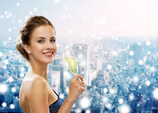 Smiling woman holding glass of sparkling wine. Drinks, christmas, holidays and people concept - smiling woman in evening dress with glass of sparkling wine over Stock Photos