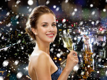 Smiling woman holding glass of sparkling wine. Drinks, christmas, holidays and people concept - smiling woman in evening dress with glass of sparkling wine over Royalty Free Stock Image