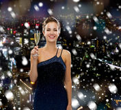 Smiling woman holding glass of sparkling wine. Drinks, holidays, christmas, people and celebration concept - smiling woman in evening dress with glass of Royalty Free Stock Photos