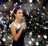 Smiling woman holding glass of sparkling wine. Drinks, holidays, christmas, people and celebration concept - smiling woman in evening dress with glass of Stock Photography