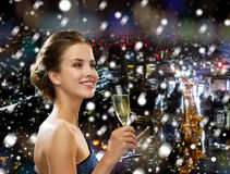 Smiling woman holding glass of sparkling wine. Drinks, holidays, christmas, people and celebration concept - smiling woman in evening dress with glass of Royalty Free Stock Images