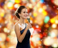 Smiling woman holding glass of sparkling wine. Drinks, holidays, christmas, people and celebration concept - smiling woman in evening dress with glass of Royalty Free Stock Photography