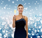 Smiling woman holding glass of sparkling wine. Drinks, holidays, christmas, people and celebration concept - smiling woman in evening dress with glass of Stock Photos