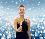 Smiling woman holding glass of sparkling wine. Drinks, holidays, christmas, people and celebration concept - smiling woman in evening dress with glass of Stock Images
