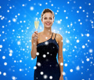 Smiling woman holding glass of sparkling wine. Drinks, holidays, christmas, people and celebration concept - smiling woman in evening dress with glass of Stock Image
