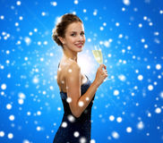 Smiling woman holding glass of sparkling wine. Drinks, holidays, christmas, people and celebration concept - smiling woman in evening dress with glass of Royalty Free Stock Image