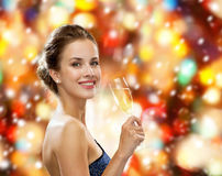Smiling woman holding glass of sparkling wine. Drinks, winter holidays, luxury and celebration concept - smiling woman in evening dress with glass of sparkling Stock Image