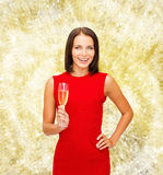 Smiling woman holding glass of sparkling wine. Party, drinks, holidays, christmas and celebration concept - smiling woman in red dress with glass of sparkling Stock Image