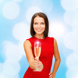 Smiling woman holding glass of sparkling wine. Party, drinks, holidays, christmas and celebration concept - smiling woman in red dress with glass of sparkling Royalty Free Stock Images