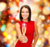Smiling woman holding glass of sparkling wine. Party, drinks, holidays, christmas and celebration concept - smiling woman in red dress with glass of sparkling Stock Photos