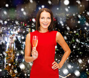Smiling woman holding glass of sparkling wine. Party, drinks, holidays, christmas and celebration concept - smiling woman in red dress with glass of sparkling Stock Photo