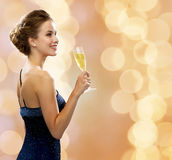 Smiling woman holding glass of sparkling wine. Party, drinks, holidays, luxury and celebration concept - smiling woman in evening dress with glass of sparkling Stock Photo