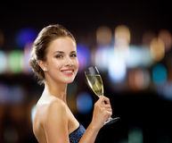 Smiling woman holding glass of sparkling wine. Party, drinks, holidays, luxury and celebration concept - smiling woman in evening dress with glass of sparkling Royalty Free Stock Photography