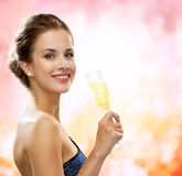 Smiling woman holding glass of sparkling wine. Party, drinks, holidays, luxury and celebration concept - smiling woman in evening dress with glass of sparkling Stock Photography