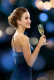 Smiling woman holding glass of sparkling wine. Party, drinks, holidays, luxury and celebration concept - smiling woman in evening dress with glass of sparkling Royalty Free Stock Images