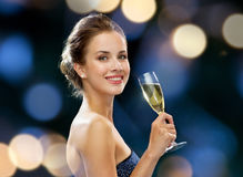 Smiling woman holding glass of sparkling wine. Party, drinks, holidays, luxury and celebration concept - smiling woman in evening dress with glass of sparkling Stock Images