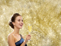 Smiling woman holding glass of sparkling wine. Party, drinks, holidays, luxury and celebration concept - smiling woman in evening dress with glass of sparkling Royalty Free Stock Photo