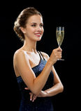 Smiling woman holding glass of sparkling wine. Party, drinks, holidays, luxury and celebration concept - smiling woman in evening dress with glass of sparkling Royalty Free Stock Image