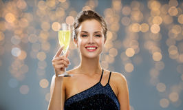 Smiling woman holding glass of sparkling wine. Party, drinks, holidays, luxury and celebration concept - smiling woman in evening dress with glass of sparkling Stock Image
