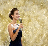 Smiling woman holding glass of sparkling wine. Party, drinks, holidays, people and celebration concept - smiling woman in evening dress with glass of sparkling Stock Image