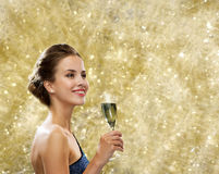 Smiling woman holding glass of sparkling wine. Party, drinks, holidays, people and celebration concept - smiling woman in evening dress with glass of sparkling Stock Images