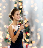 Smiling woman holding glass of sparkling wine. Party, drinks, holidays, people and celebration concept - smiling woman in evening dress with glass of sparkling Royalty Free Stock Photo