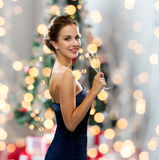 Smiling woman holding glass of sparkling wine. Party, drinks, holidays, people and celebration concept - smiling woman in evening dress with glass of sparkling Royalty Free Stock Image