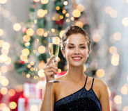 Smiling woman holding glass of sparkling wine. Party, drinks, holidays, people and celebration concept - smiling woman in evening dress with glass of sparkling Stock Photo