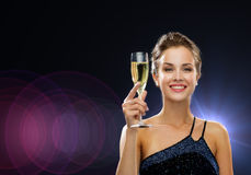 Smiling woman holding glass of sparkling wine. Party, drinks, holidays, people and celebration concept - smiling woman in evening dress with glass of sparkling Stock Photography