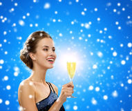 Smiling woman holding glass of sparkling wine. Party, drinks, winter holidays, christmas and celebration concept - smiling woman in evening dress with glass of Royalty Free Stock Photos